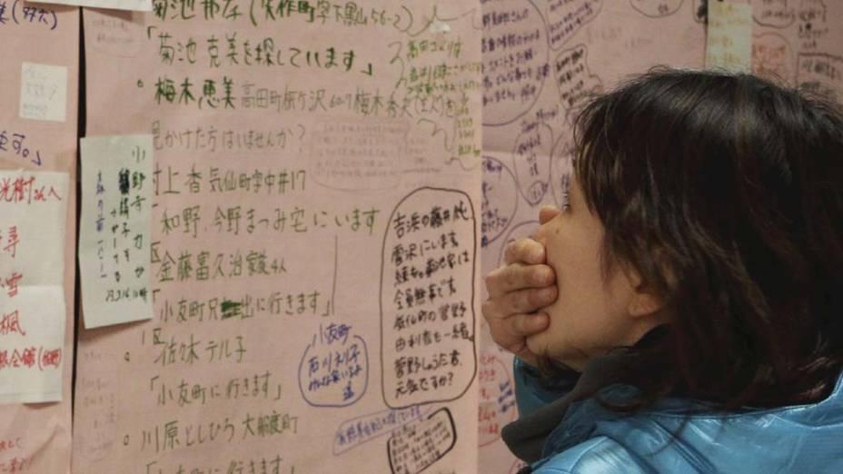 Mulher olha quadro de mensagens das pessoas que evacuaram a cidade Rikuzentakata, no Japão