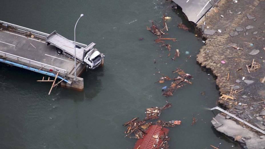 Caminhão pendurado em uma ponte que desabou em Ishinomaki, após terremoto e tsunami que atingiram o Japão