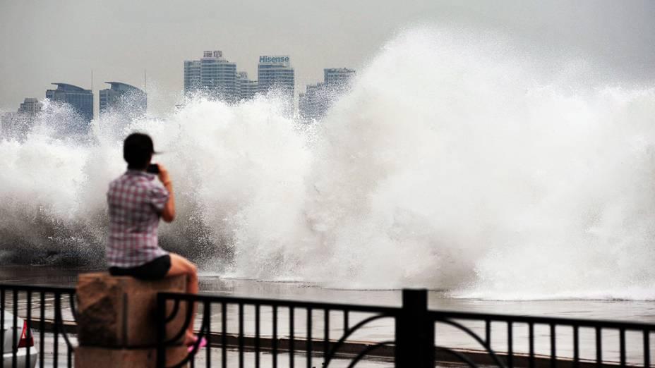 Jovem observa onda gigante em Qingdao, na China, provocada pela passagem do tufão Bolaven pela região