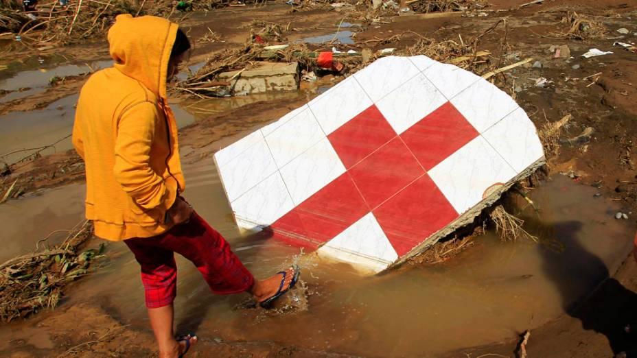 Mulher anda entre destroços da Cruz Vermelha, em Cagayn de Oro, após a região ser atingida por tufão - 18/12/2011