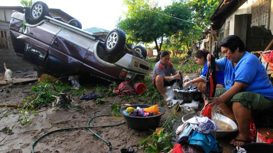 Mulheres lavam roupas ao lado de carro atingido por tufão, em Cagayan de Oro, nas Filipinas - 18/12/2011