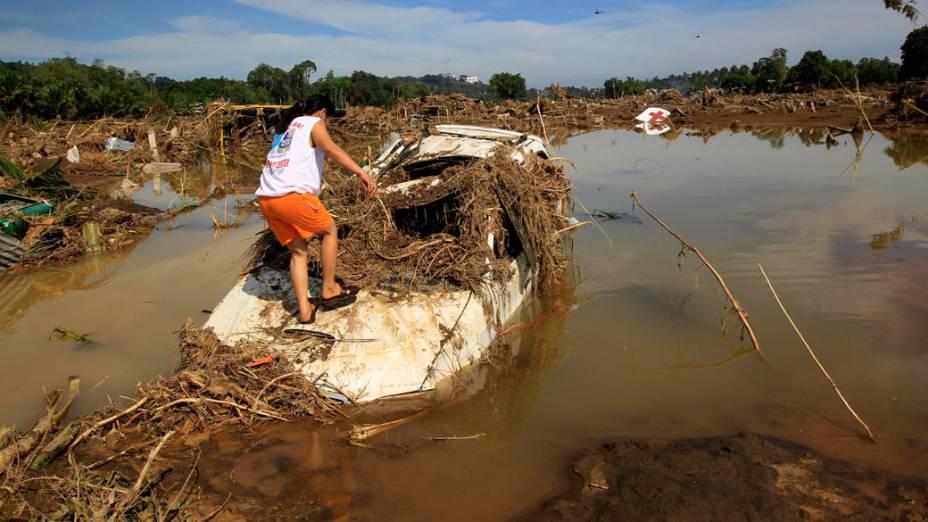 Mulher anda entre destroços, após tufão atingir a região de Cagayan de Oro, nas Filipinas - 18/12/2011
