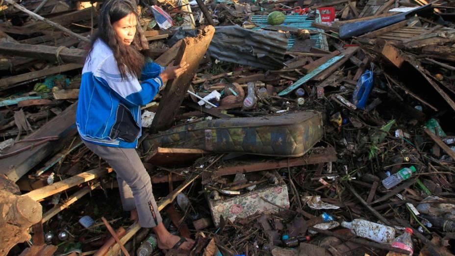Moradora da região de Cagayan de Oro, atingida por tufão, anda por destroços - 18/12/2011