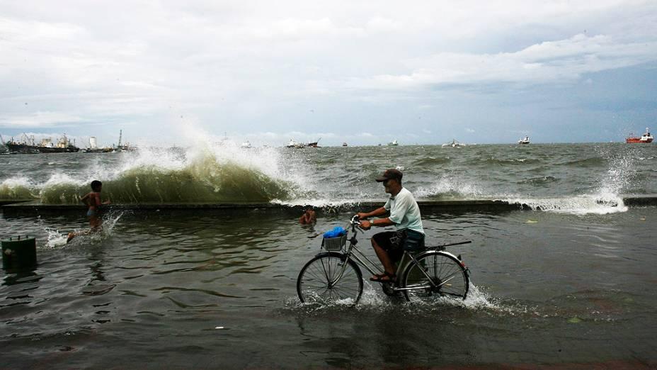 Ciclista passa por rua alagada durante passagem do tufão Mawar por Manila, nas Filipinas; 5 pessoas estão desaparecidas