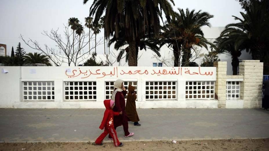 Família caminha em frente as marcas deixadas pelos protestos em Tunis