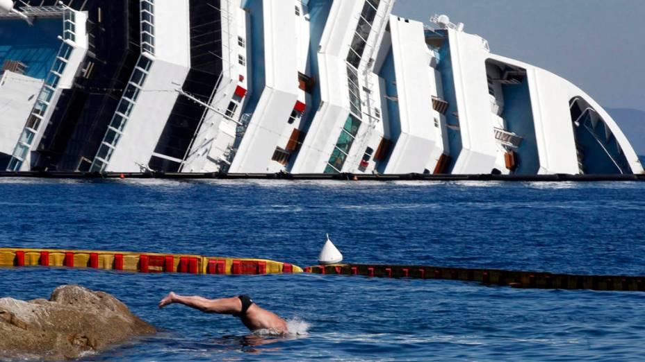 Turistas desfrutam praia, próximo do navio Costa Concordia que naufragou, na Espanha