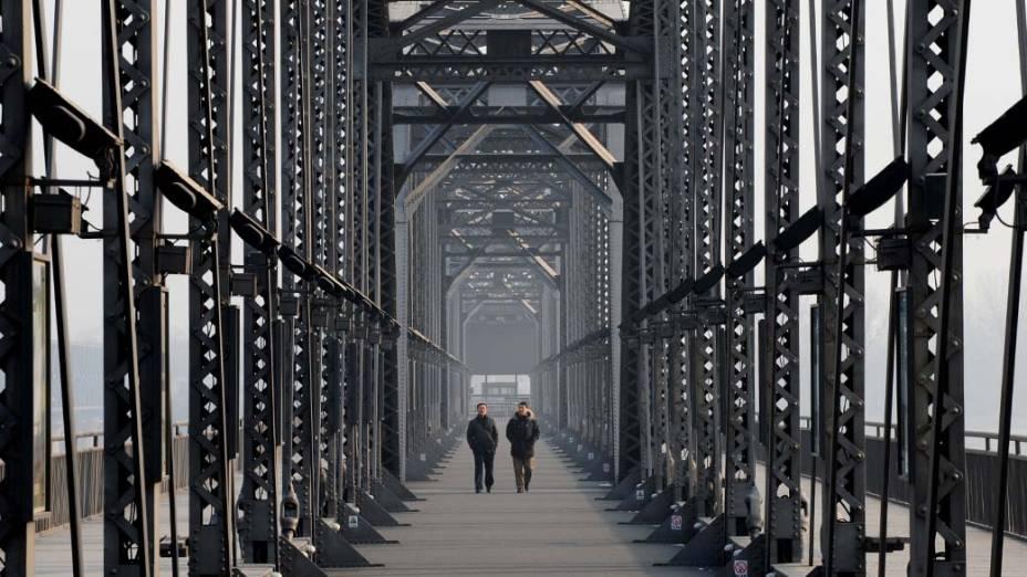 Turistas caminham na antiga Ponte Yalu, China