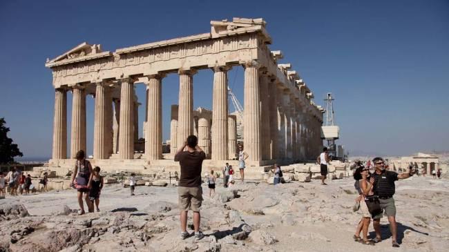 Turistas visitam o Partenon, na Acrópole de Atenas, Grécia