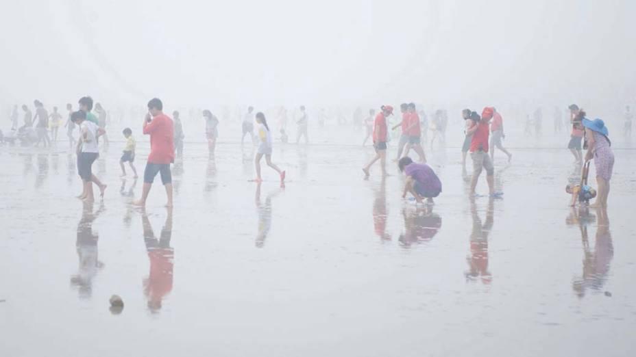 Turistas aproveitam praia em dia nublado na cidade chinesa de Qingdao