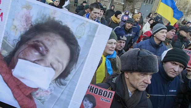 Manifestantes mostram foto da jornalista e ativista Tetyana Chornovil, espancada horas depois de publicar fotos sobre integrantes do governo na Ucrânia