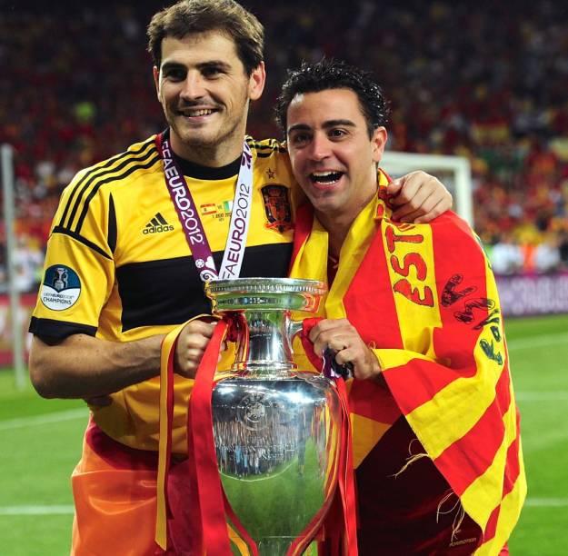Rivais unidos na seleção espanhola: Casillas, com a bandeira da Espanha, e Xavi, com a da Catalunha