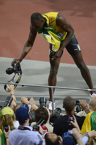 """Usain Bolt """"rouba"""" máquina de fotógrafos na comemoração do bicampeonato olímpico dos 200 m rasos, em Londres"""