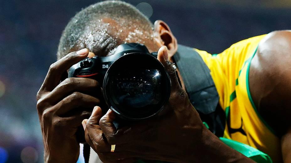 Usain Bolt tira foto com câmera de fotógrafo após a conquista dos 200 m rasos em Londres