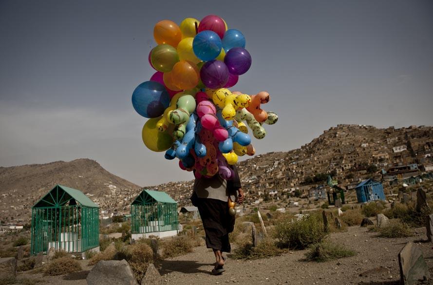 Vendedor de balões anda por cemitério da cidade velha de Cabul