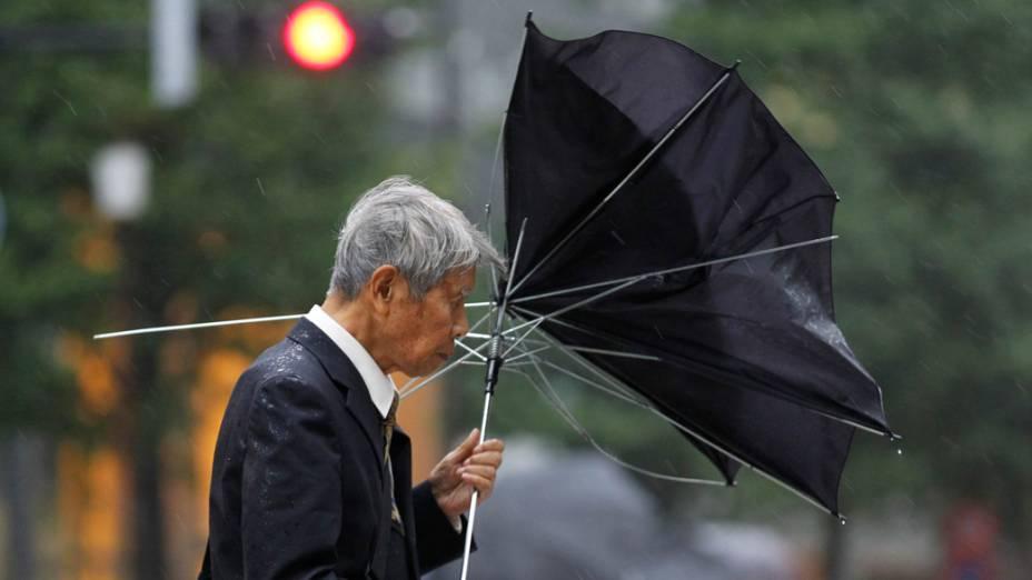 No Japão, pedestre caminha pelas ruas de Tóquio durante ventania provocada pelo tufão Roke