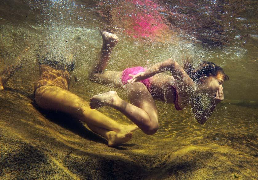 Menina e sua mãe nadam em lago da reserva natural Step Falls, no estado americano de Maine, no nordeste do país