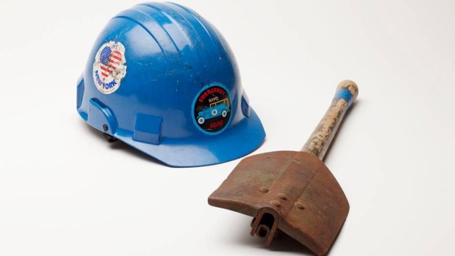 Capacete e pá do Departamento de Polícia de Nova York, utilizado pela policial Kenny Winkler, durante o período de limpeza do marco zero, após o atentado de 11 de setembro