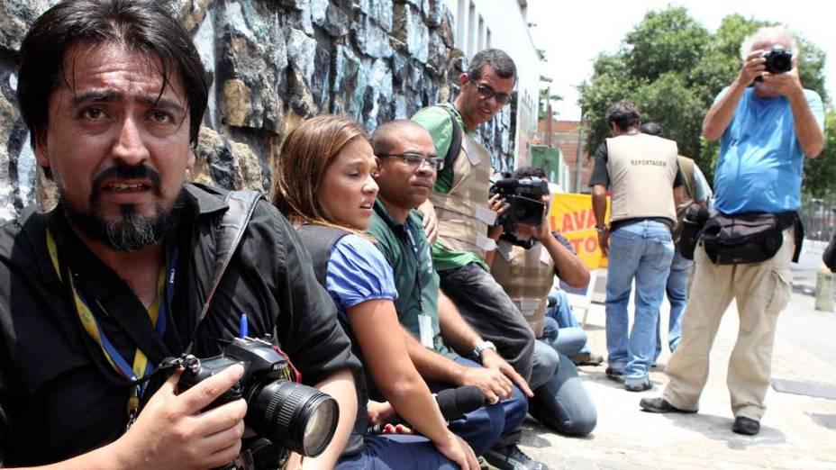 Na quinta-feira, dia 25 de novembro, jornalistas se protegem na Vila Cruzeiro, Rio de Janeiro