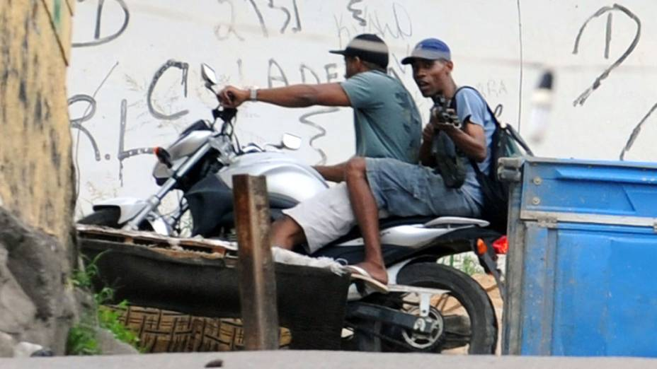 Traficantes passam de motocicleta por rua do Complexo do Alemão, no Rio de Janeiro. 27/11/2010