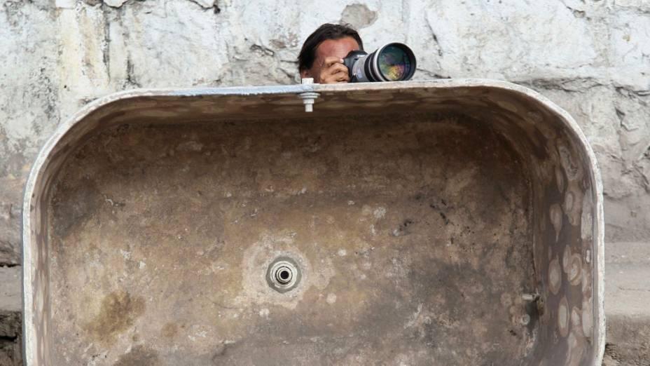 Fotógrafo protege-se atrás de caixa dágua durante troca de tiros no Complexo do Alemão - 28/11/2010