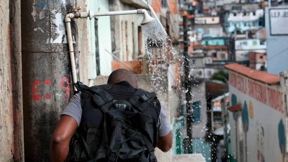 Policial limpa o rosto durante a invasão ao Complexo do Alemão  - 28/11/2010
