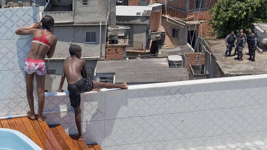 Crianças brincam na piscina da casa do traficante carioca, após a polícia desocupar o local - 28/11/2010