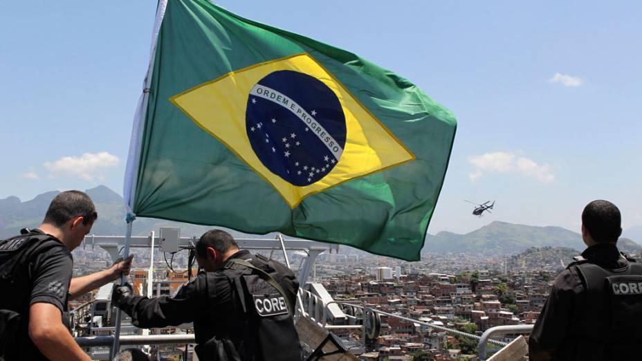 Policiais hasteiam a bandeira nacional em uma das estações do teleférico financiado pelo PAC no Complexo do Alemão, no Rio de Janeiro - 28/11/2010