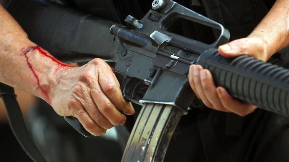 Detalhe das mãos de policial sangrando durante a invasão da favela da Grota no Complexo do Alemão, no Rio de Janeiro - 28/11/2010