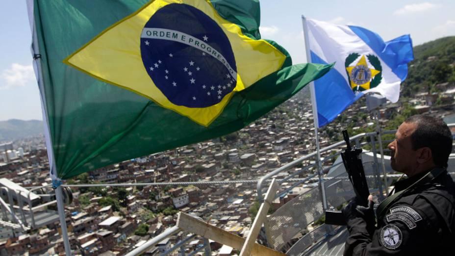 Policiais hasteiam a bandeira do Brasil e a do Estado do Rio de Janeiro no largo dos Coqueiros, no alto do Complexo do Alemão, no Rio de Janeiro - 28/11/2010