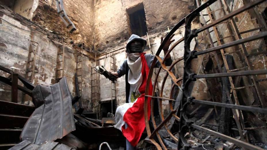 Voluntário recupera manuscritos queimados nas ruínas do Instituto do Egito após incêndio causado por confrontos da praça Tahrir, no Cairo
