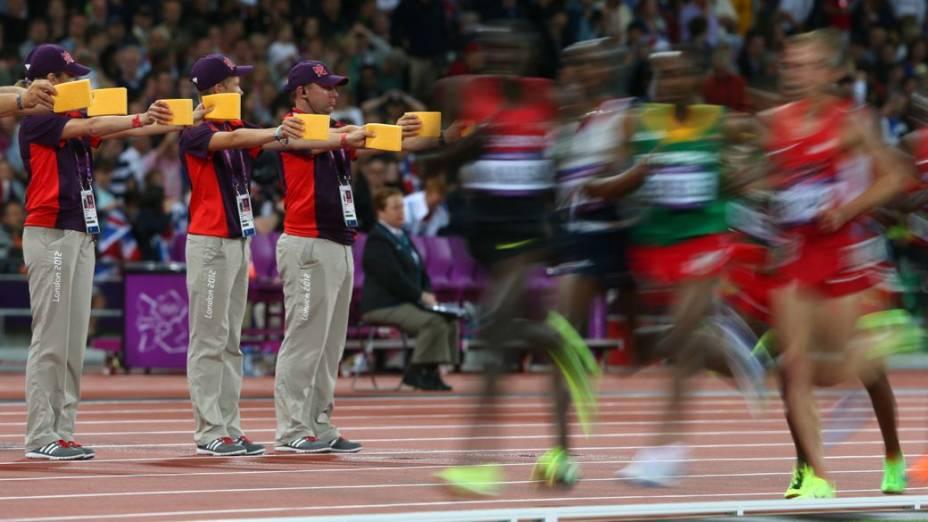 Voluntários na pista de atletismo do Estádio Olímpico de Londres