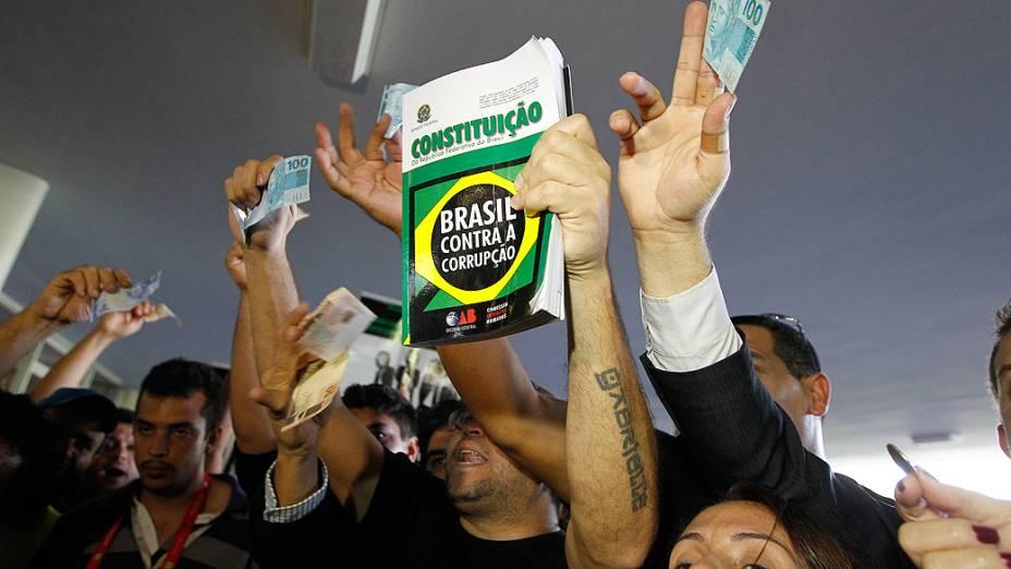 Manifestantes mostram a Constituição e notas de dinheiro em protesto contra a votação da mudanças feitas pelo governo federal na LDO tentam entrar no Congresso Nacional e são barrados pela segurança da Casa