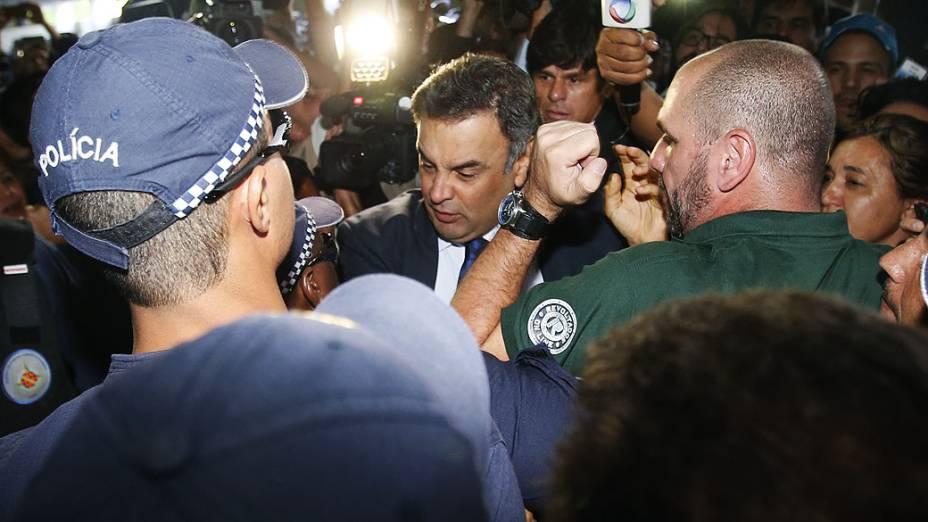 O senador Aécio Neves (PSDB-MG) chega ao Congresso Nacional, em Brasília, passando por manifestantes contrários à aprovação da alteração da meta fiscal