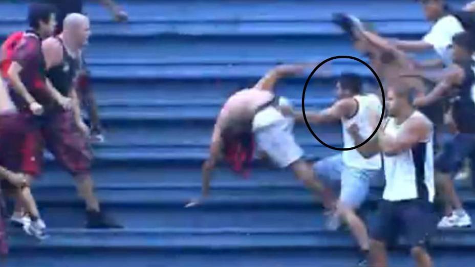 NNaíba - de bermuda azul - puxa um torcedor rival e troca socos durante a pancadaria na Arena Joinville. Bruno Fet, de camisa branca com listras pretas, parte para a briga