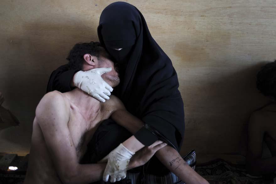 """Foto do Ano de 2011 para o """"World Press Photo Award"""", do espanhol Samuel Aranda, mostra mulher segurando ferido durante protestos contra o ditador Ali Abdullah Saleh, no Iêmen"""
