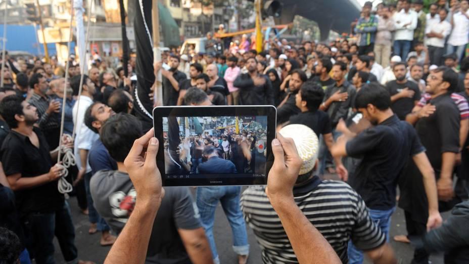 Muçulmano xiita usa tablet para fazer vídeo de procissão religiosa durante Muharram em Mumbai, Índia