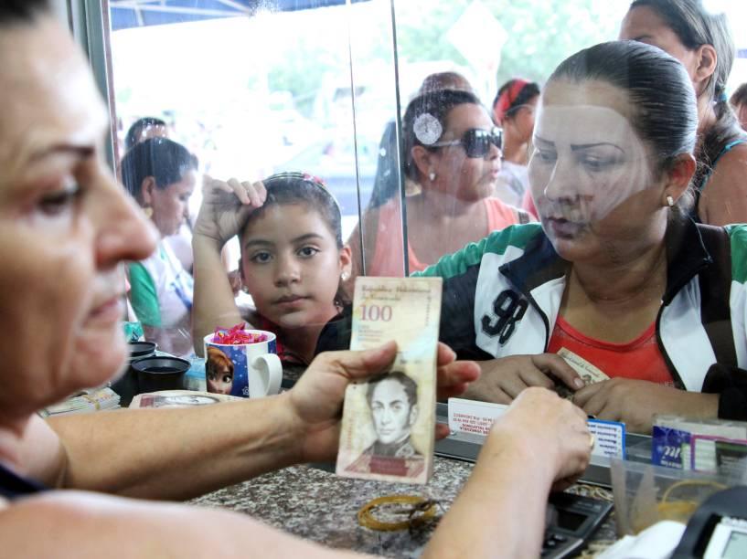 Cidadãos venezuelanos trocam dinheiro em uma casa de câmbio em Villa del Rosario perto de Cucuta, na Colômbia - 10/07/2016