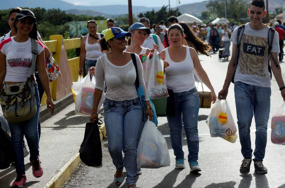 Venezuelanos carregam sacolas de mantimentos após aproveitarem a abertura temporária de fronteira com a Colômbia para fazer compras no país vizinho - 10/07/2016