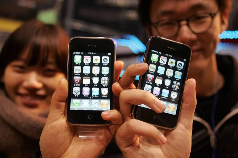 Sul-coreanos mostram o iPhone 3Gs que acabaram de comprar após uma longa fila de espera, em 2009