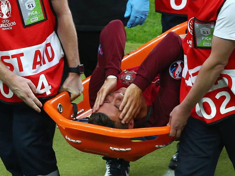 O português Cristiano Ronaldo chora após sofrer lesão e deixar o campo de maca
