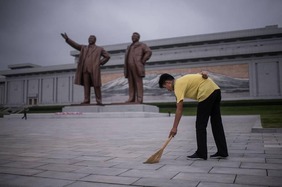 Funcionário faz serviço voluntário varrendo o chão em frente às estátuas que homenageiam os ditadores Kim Il-Sung e Kim Jong-Il, em Pyongyang, Coreia do Norte