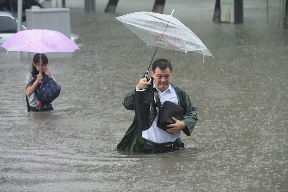 Homem e menina seguram guarda-chuvas enquanto caminham por uma enchente, depois de fortes tempestades atingirem a região da província de Shanxi, na China - 19/07/2016
