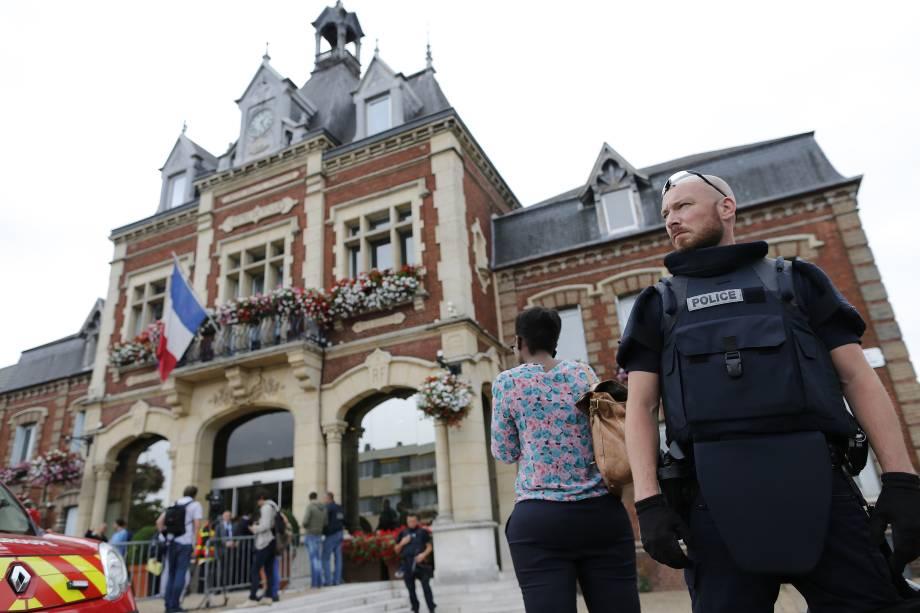 Agente da polícia fica de guarda em frente à prefeitura de Saint-Etienne-du-Rouvray, norte da França, na sequência de uma tomada de reféns em uma igreja que terminou com a morte de um padre - 26/07/2016