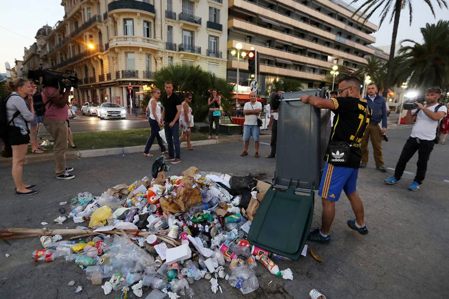"""População francesa faz """"memorial de ódio"""" no local onde o atirador de Nice foi morto pela polícia no Dia da Bastilha. Na foto, homem revira uma lata de lixo como forma de protesto - 19/07/2016"""
