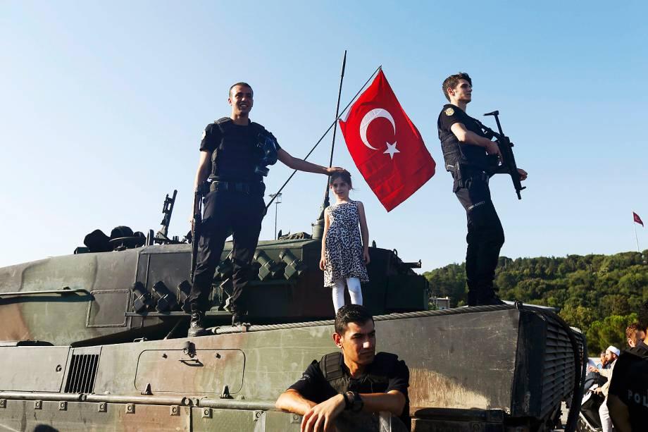 Uma criança é fotografada ao lado de policiais turcos em tanque usado em tentativa de golpe