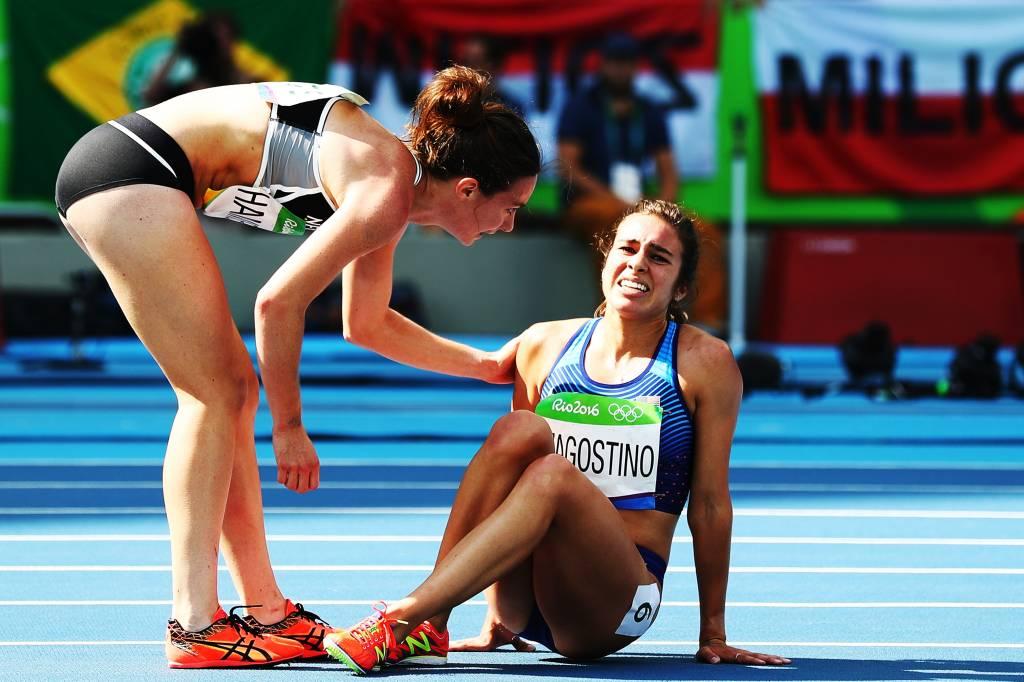Abbey D'Agostino dos Estados Unidos (à dir.) é ajudada pela neozelandesa Nikki Hamblin depois de uma colisão entre as duas durante a prova dos 5.000 metros rasos