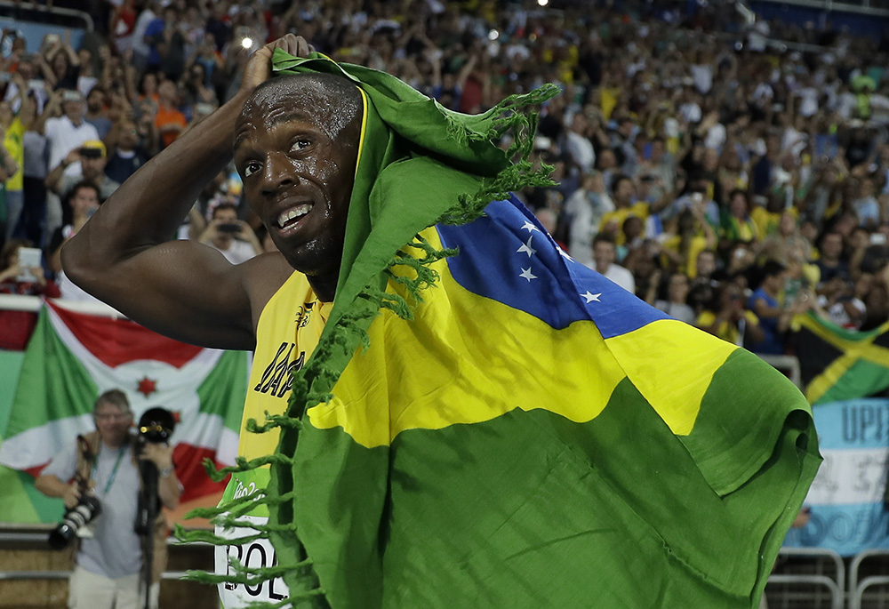 Usain Bolt from Jamaica celebrates winning the gold medal in the men's 200-meter final, with the Brazilian flag, during the athletics competitions of the 2016 Summer Olympics at the Olympic stadium in Rio de Janeiro, Brazil, Thursday, Aug. 18, 2016. (AP Photo/Matt Slocum)