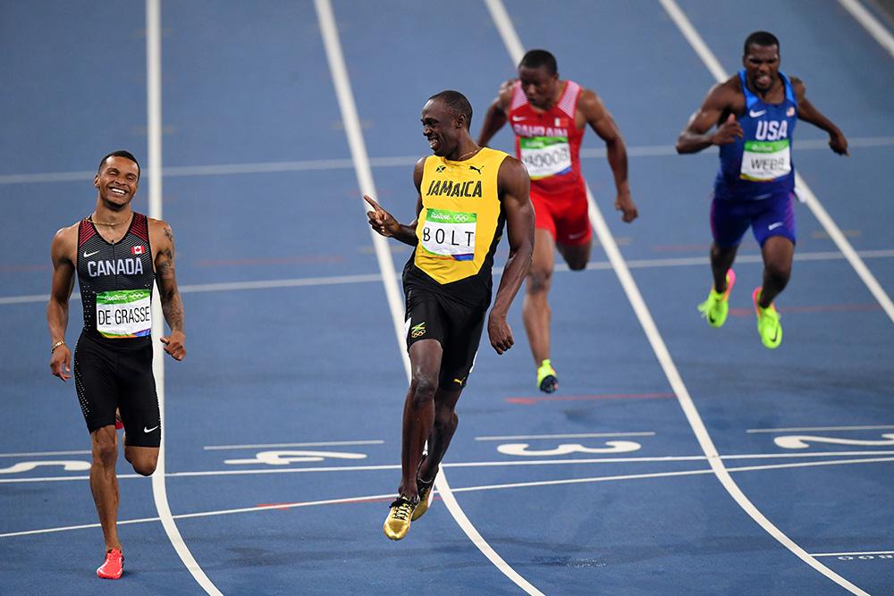 O jamaicano Usain Bolt sorri ao lado do canadense Andre De Grasse após terminarem a seletiva dos 200 m. Bolt ganhou e De Grasse ficou em segundo