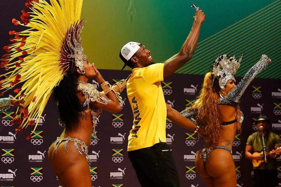 O velocista Usain Bolt dança com passistas durante uma coletiva de imprensa, no Rio