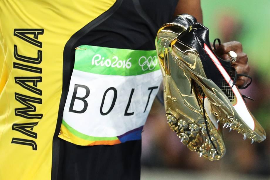 Usain Bolt segura suas sapatilhas douradas após conquistar o tri olímpico nos 100m rasos